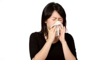 A woman with her eyes closed is holding a tissue to her nose.