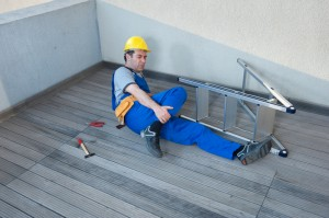 A man wearing a hard hat is lying on the ground next to a fallen ladder while holding his leg
